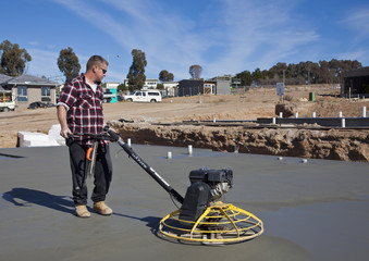 Workman smoothing newly poured concrete for housing estate