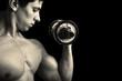 Closeup of a muscular young man lifting weights