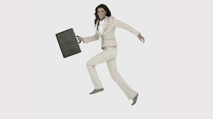 Businesswoman jumping in the air with her suitcase