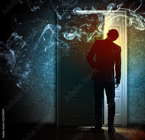 Young businessman opening door