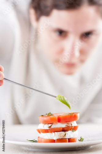 Cook serving mozzarella and tomato slices close-up