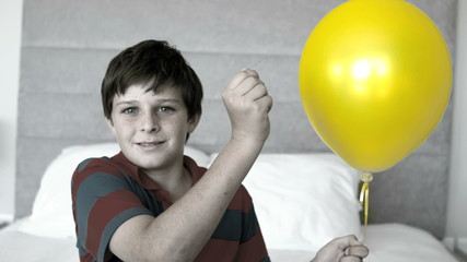 Boy piercing his balloon in the bedroom in selective color