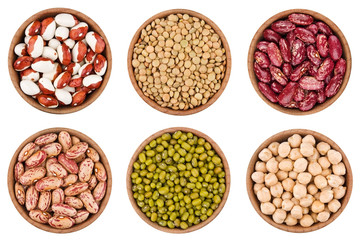 Assortment of legumes in wooden bowls isolated on white