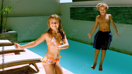 Young girl dancing while brother jumping in the swimming pool