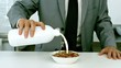 Well dressed businessman pouring milk into his cereals