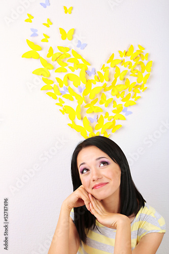 Girl near paper butterflies fly on wall