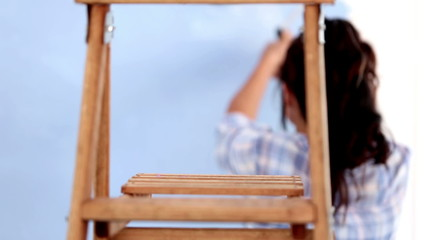 Attractive woman jumping to paint her wall then resting