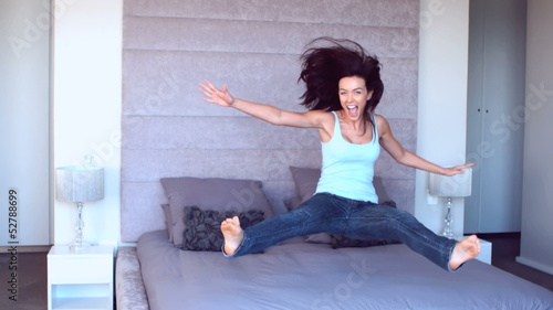 Pretty woman jumping onto bed