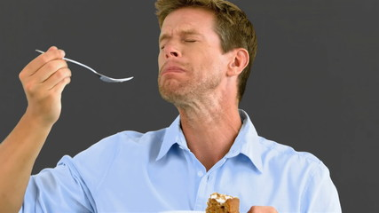 Man savouring a delicious cake on grey screen