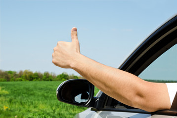Man inside car showing thumb up
