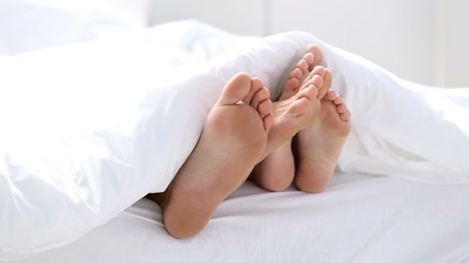 Pair of feet playing footsie under the covers