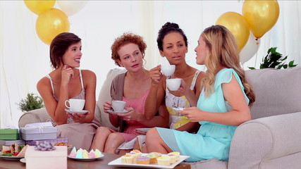 Friends drinking tea and chatting at a party