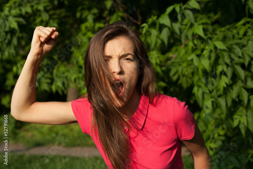 Angry girl shouting and holding her fist, want to attack