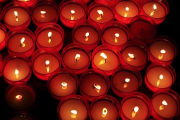 Candele votive rosse illuminano il buio in chiesa