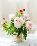 Delicate peonies in a water can