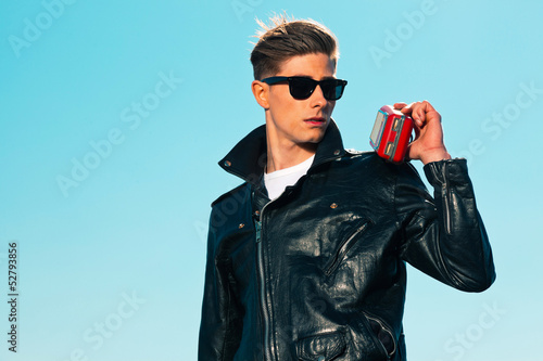 Retro fifties rockabilly man with black jacket listens to portab