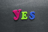 word yes spelled out using colored fridge magnets