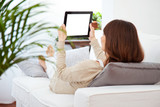 Young woman lying on the couch and working with a digital tablet