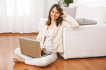 Young woman sitting on floor with a laptop