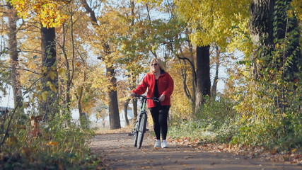 woman with a bicycle is in the autumn park