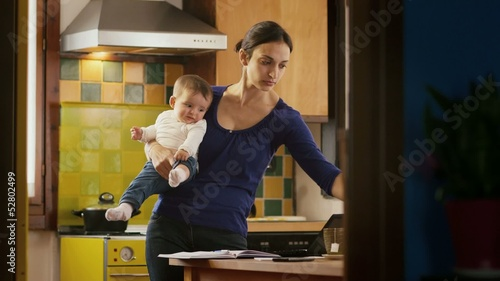 Multitasking mother working with pc, holding little girl at home