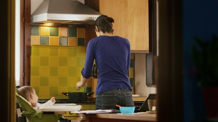 Multi-tasking mom cooking, working, feeding child in kitchen