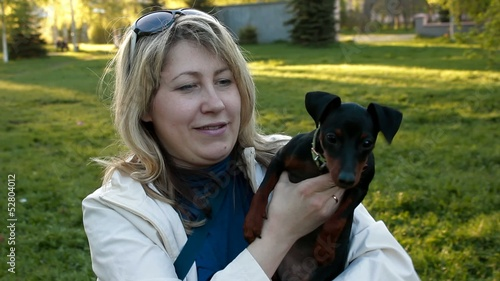 girl holding a miniature pinscher puppy