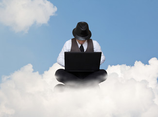 Businessman working on a cloud.