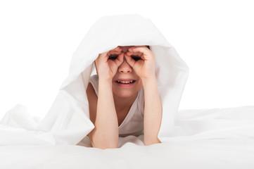 cheerful boy hiding under blanket