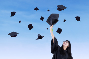 Asian graduate throw graduation cap in air