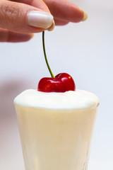 mano che immerge una ciliegia nello yogurt bianco
