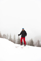 Happy ski man with blue hat standing in snow.