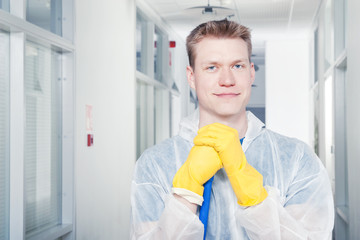 Smiling office cleaner wearing protective overalls