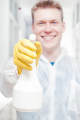 Office cleaner man pointing camera with spray bottle