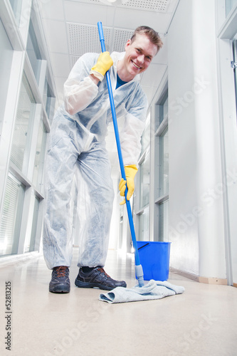 Man cleaning office wearing protective overalls