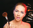 young woman holds the make-up brushes near attractive face.