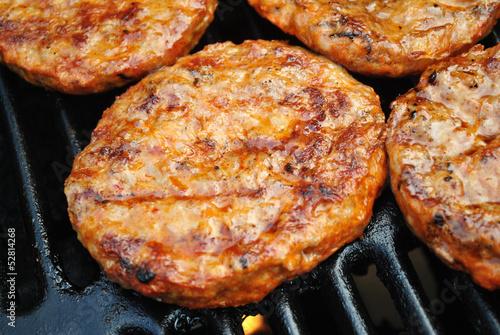 Leinwanddruck Bild Spicy Sausage Patties Cooking on a Summer Grill