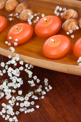 Beautiful candles in water on wooden table close-up