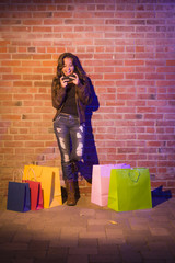 Woman with Shopping Bags Using Cell Phone Against Brick Wall