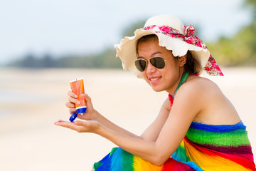 Sunscreen woman. Girl sun block on beach holding