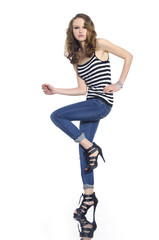 Full body young woman in stripy shirt and jeans posing