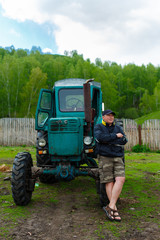 Portrait farmer standing in front of his old tractor