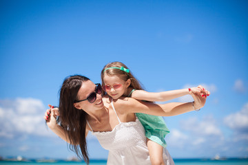 Young beautiful mother and her adorable little daughter at