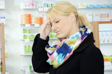 Junge Frau mit Kopfschmerz in Apotheke