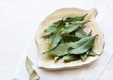 Bay leaves on plate over light background