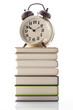 積み上げた本と目覚し時計