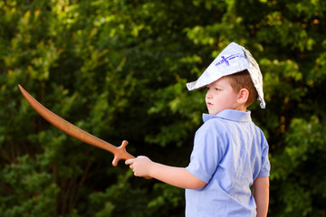 Child playing pirate outdoors in homemade costume
