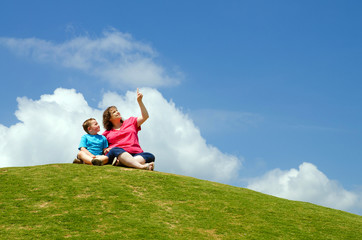 Mother and son watching clouds from grassy hill