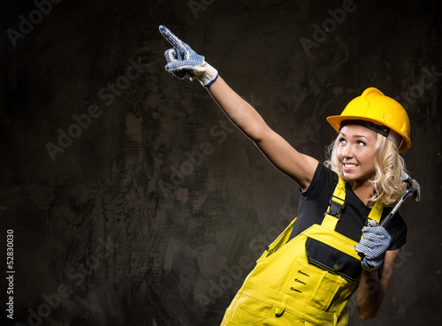 Attractive builder woman showing something with the hand