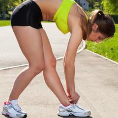 Beautiful woman in fitness wear ties shoelaces